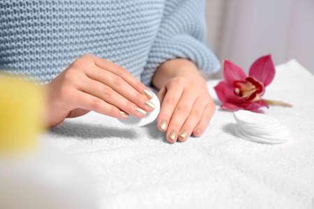 Woman removing nail polish on towel, closeup