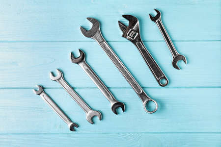 New wrenches on color background, top view. Plumber tools