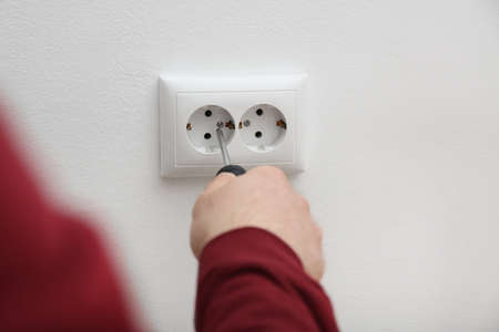 Electrician repairing wall sockets on white background, closeup Foto de archivo - 119138571