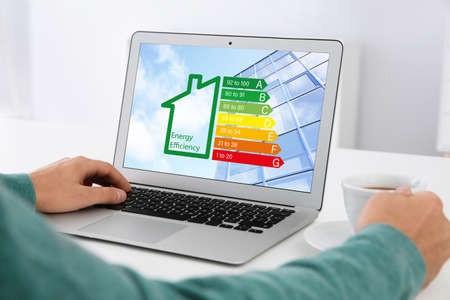 Man working with modern laptop at table, closeup. Energy efficiency concept