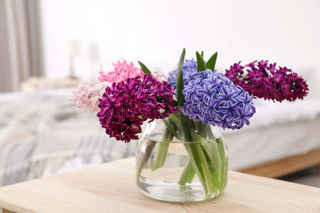 Beautiful hyacinths in glass vase on table indoors. Spring flowers Stock Photo