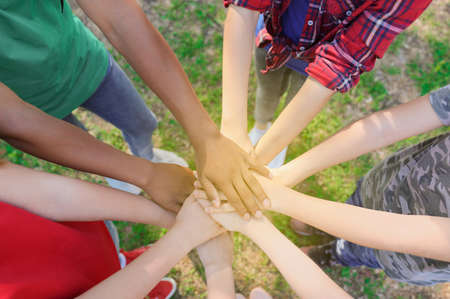 Group of volunteers putting hands together outdoors, top view Imagens