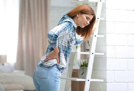 Young woman suffering from back pain at home