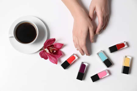 Woman with gold manicure holding hands near nail polishes and cup of coffee on white background, top view Stock Photo