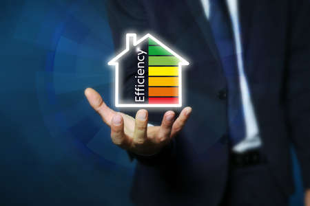 Businessman holding house icon with energy efficiency rating against color background, closeup