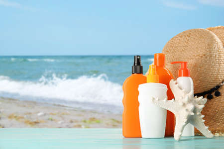 Set with different bottles of sun protection body cream and hat on wooden table against seascape. Space for design