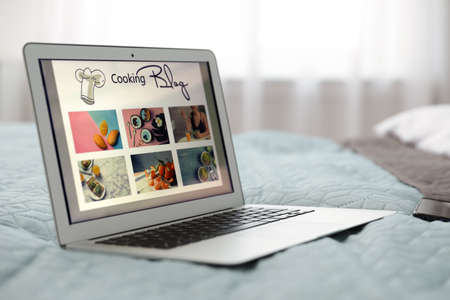Modern laptop with open cooking blog on bed