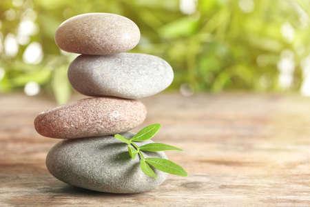 Spa stenen en bamboe bladeren op tafel tegen onscherpe achtergrond, ruimte voor tekst. Zen, balans, harmonie Stockfoto