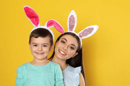 Mother and son in Easter bunny ears headbands on color background, space for text