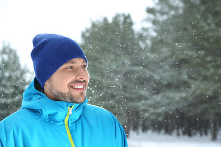 Portrait of happy man in snowy forest. Space for text