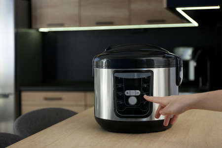 Woman turning on modern electric multi cooker in kitchen, space for text