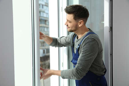Professional construction worker installing window in apartment Stock Photo
