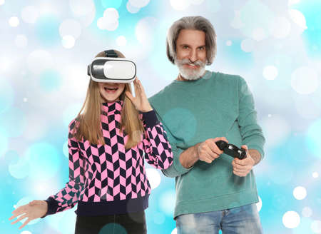 Senior man and his granddaughter playing video games against color background