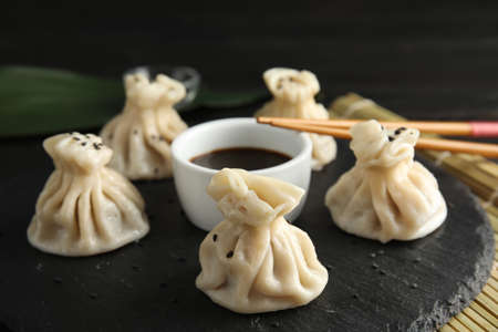 Slate plate with tasty baozi dumplings, chopsticks and soy sauce on table Фото со стока
