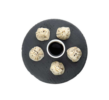 Slate plate with tasty baozi dumplings and soy sauce on white background, top view 免版税图像