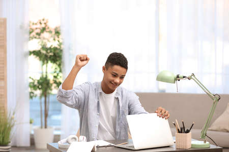 Emotional African-American teenage boy with laptop at table in room Stock Photo