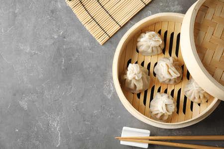 Vapeur en bambou avec de savoureuses boulettes de baozi sur table, vue de dessus. Espace pour le texte
