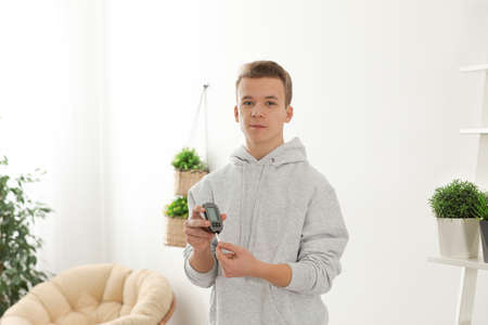 Teen boy holding digital glucometer at home. Diabetes control Banque d'images