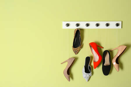 Different lady's shoes hanging on rack against color background, space for text