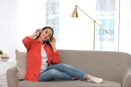 Young woman with headphones enjoying music in living room Stockfoto