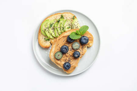 Plate of tasty toasts with avocado, blueberries and chia seeds on white background, top view