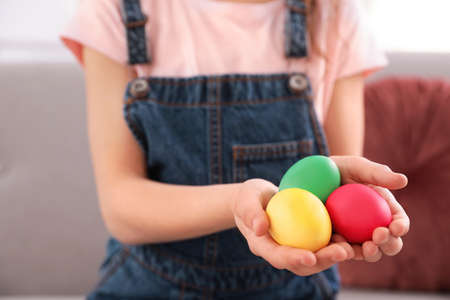 Little girl holding Easter eggs indoors, closeup. Space for text
