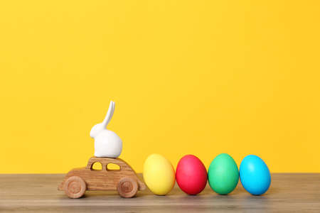 Toy car with ceramic bunny and Easter eggs on wooden table against color background
