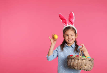 Little girl in bunny ears headband holding basket with Easter eggs on color background, space for text Reklamní fotografie