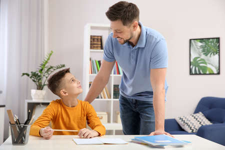 Dad helping his son with homework in room Standard-Bild