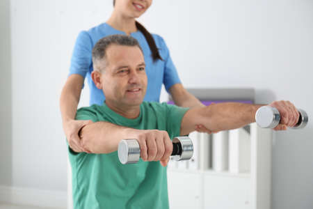 Doctor working with patient in hospital. Rehabilitation exercises