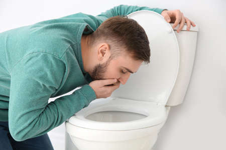 Young man suffering from nausea over toilet bowl indoors Stock Photo