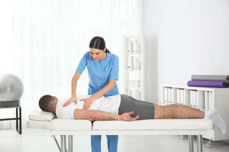 Doctor working with patient in hospital. Rehabilitation massage Foto de archivo