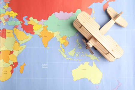 Toy airplane on world map, top view. Travel agency
