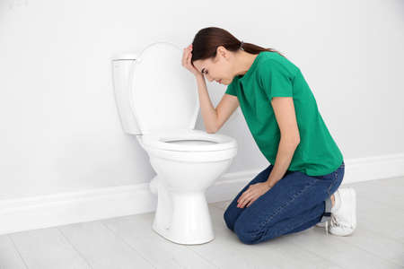 Young woman suffering from nausea at toilet bowl indoors. Space for text Reklamní fotografie