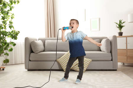 Cute funny boy with microphone in living room