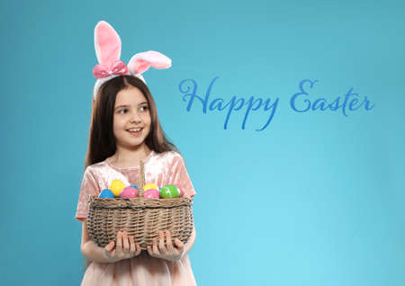 Little girl in bunny ears headband holding basket with eggs on color background. Happy Easter