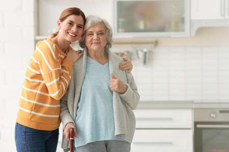 Volunteer with senior woman in kitchen. Space for text Banco de Imagens - 119900966