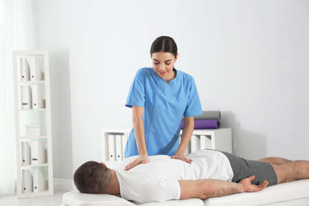 Doctor working with patient in hospital. Rehabilitation massage Imagens