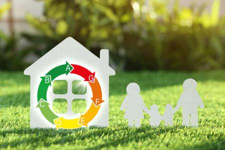 Papierausschnitt von Familie und Haus auf grünem Gras. Energieeffizienzkonzept