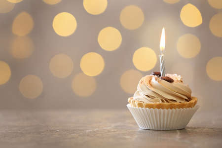 Bizcocho de cumpleaños sabroso con vela en la mesa contra luces borrosas, espacio para texto Foto de archivo