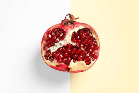 Half of ripe pomegranate on color background, top view