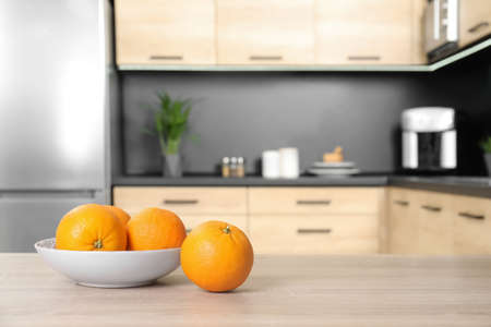 Fresh oranges on wooden table in kitchen. Space for text
