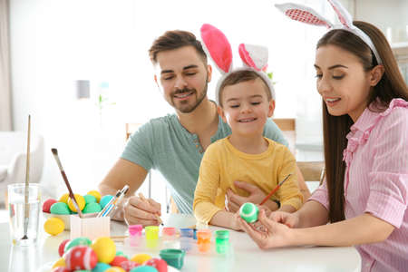 Happy family painting Easter eggs in kitchen. Festive tradition Stockfoto