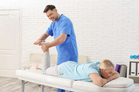 Physiotherapist working with patient in clinic. Rehabilitation therapy