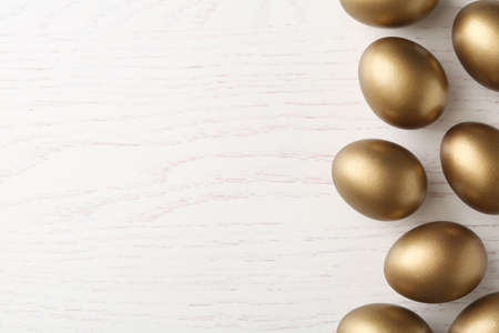 Many golden eggs and space for text on wooden background, top view