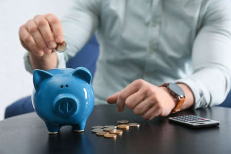 Businessman putting coin into piggy bank at table against light background, closeup. Money saving