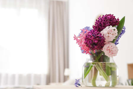 Beautiful hyacinths in glass vase on table indoors, space for text. Spring flowers
