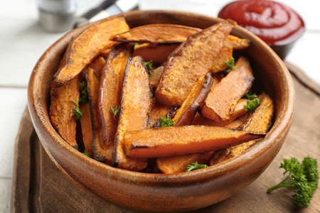 Bowl with tasty sweet potato fries on wooden board, closeup