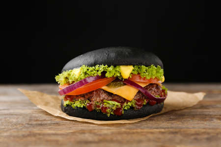 Tasty black burger on table against dark background
