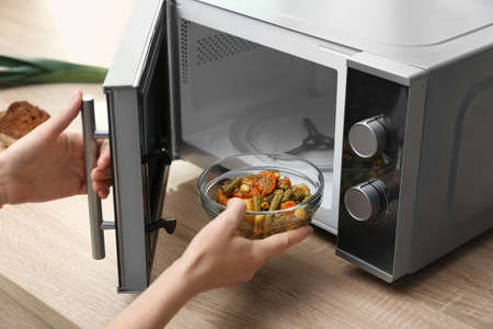 Young woman using microwave oven on table in kitchen Imagens